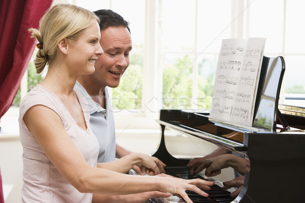 Stock photo: Couple playing piano and smiling