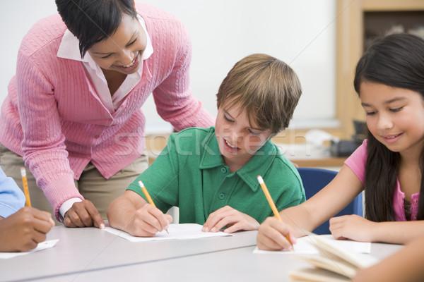 Elementary school teacher helping pupil Stock photo © monkey_business