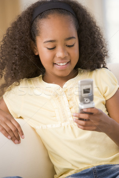 Young girl in living room using cellular phone and smiling Stock photo © monkey_business