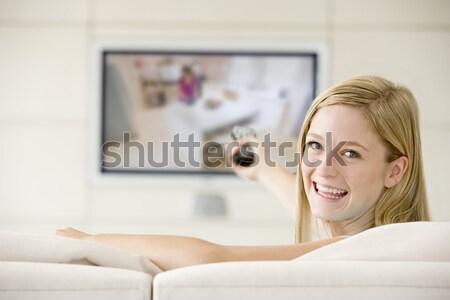 Woman in living room watching television smiling Stock photo © monkey_business