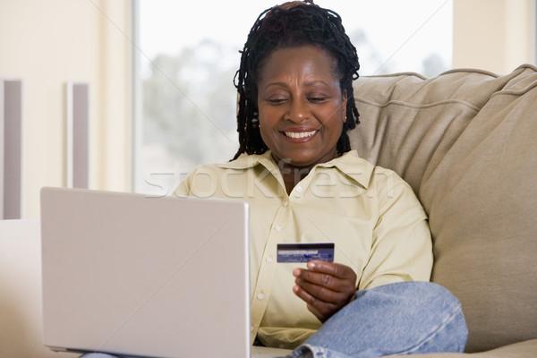 Сток-фото: женщину · гостиной · используя · ноутбук · кредитных · карт · компьютер