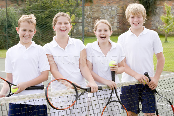 Four young friends with rackets on tennis court smiling Stock photo © monkey_business