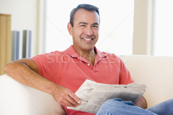 Man reading newspaper in living room smiling Stock photo © monkey_business