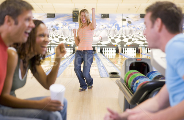 Four young adults cheering in a bowling alley Stock photo © monkey_business