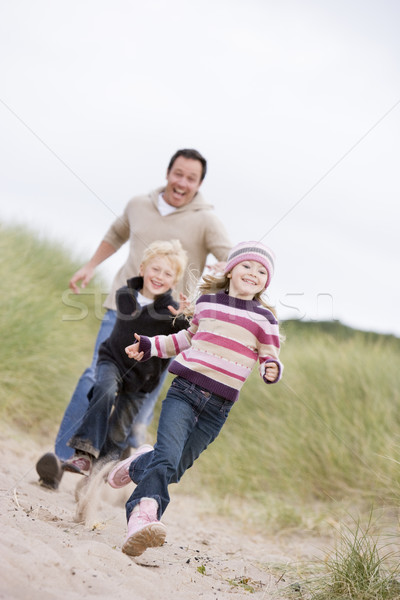 Father and two young children running at beach smiling Stock photo © monkey_business