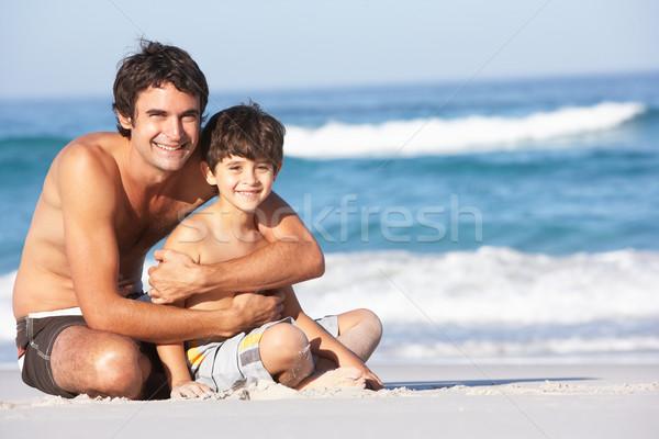 Hijo de padre sesión playa de arena playa Foto stock © monkey_business