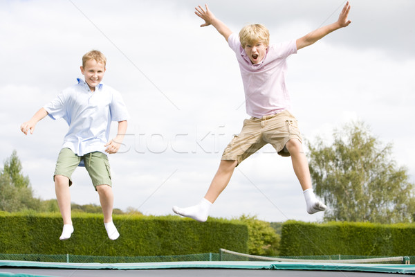 Two young boys jumping on trampoline smiling Stock photo © monkey_business