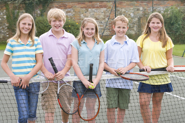 Five young friends with rackets on tennis court smiling Stock photo © monkey_business