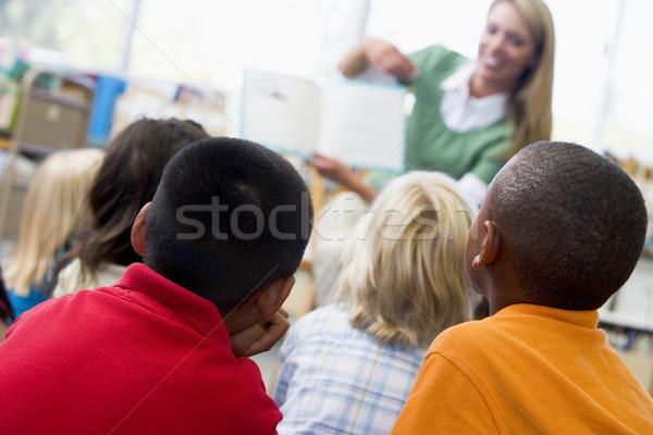 Kindergarten teacher reading to children in library Stock photo © monkey_business