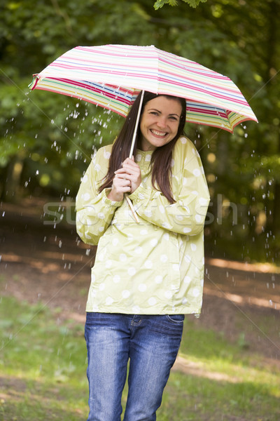 Woman outdoors in rain with umbrella smiling Stock photo © monkey_business