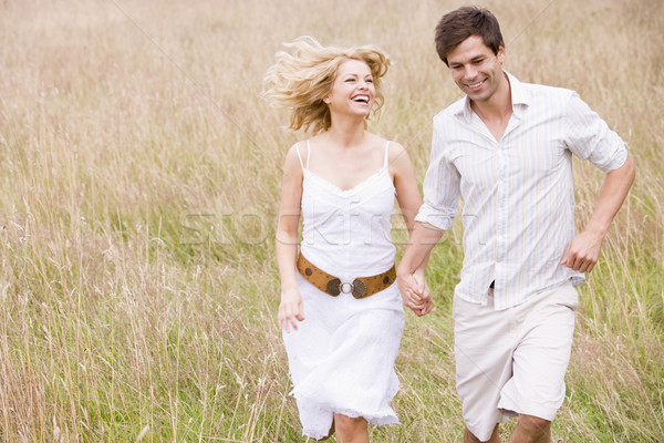 Stock photo: Couple running outdoors holding hands smiling