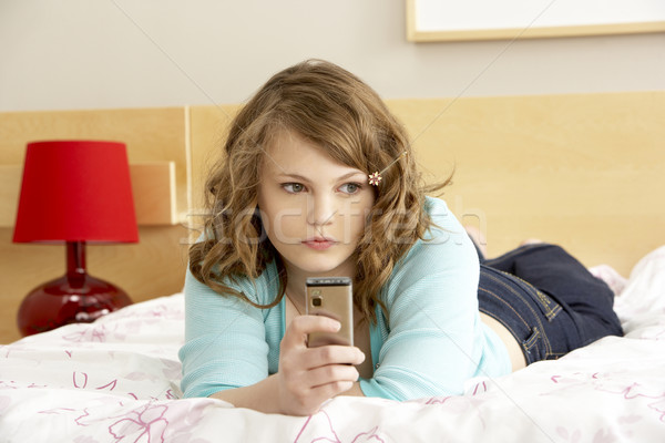 Sad Teenage Girl In Bedroom With Mobile Phone Stock photo © monkey_business