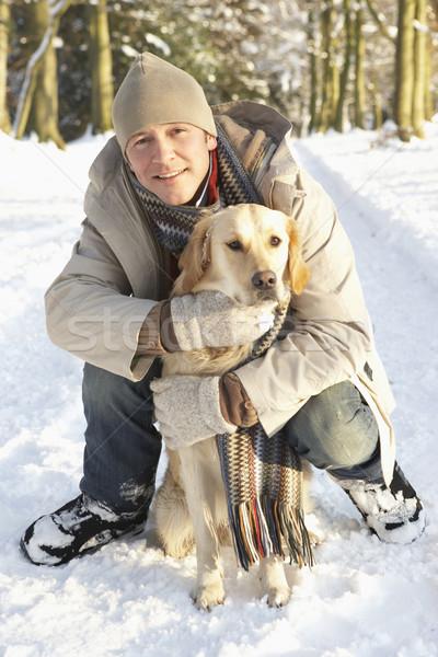 Man Walking Dog Through Snowy Woodland Stock photo © monkey_business