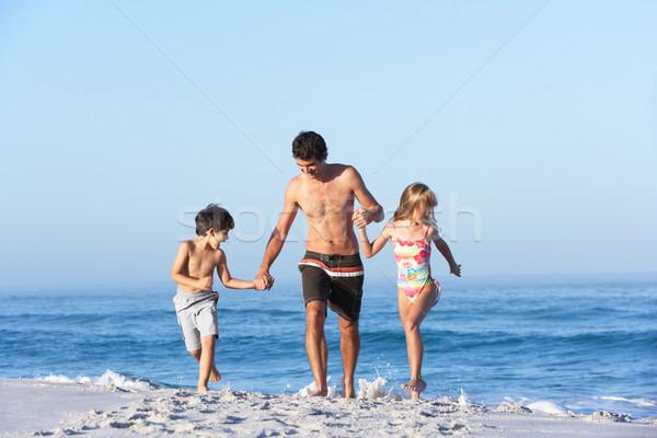 Vader lopen kinderen zandstrand familie gelukkig Stockfoto © monkey_business