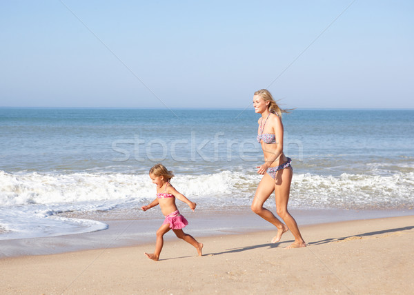 Mother chasing young girl on beach Stock photo © monkey_business