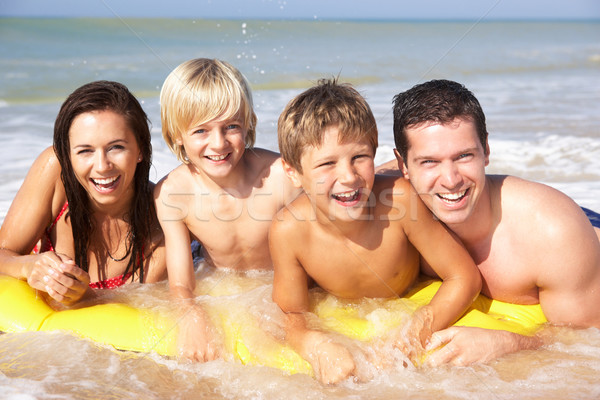 Young family pose on beach Stock photo © monkey_business