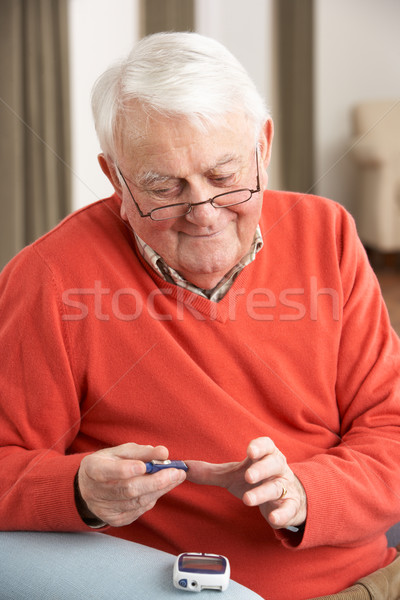 Senior Man Checking Blood Sugar Level At Home Stock photo © monkey_business