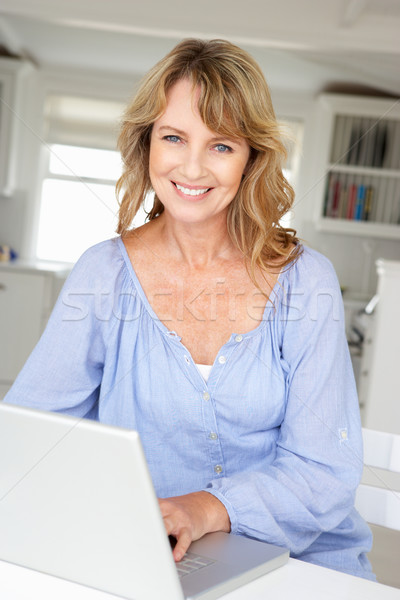 Mid age woman using laptop Stock photo © monkey_business