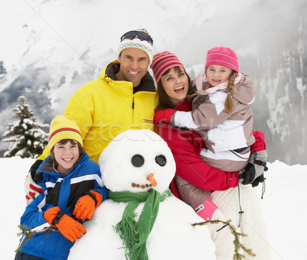 Family Building Snowman On Ski Holiday In Mountains Stock photo © monkey_business