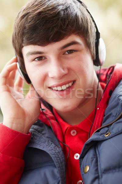Tizenéves fiú visel fejhallgató zenét hallgat tél ruházat Stock fotó © monkey_business