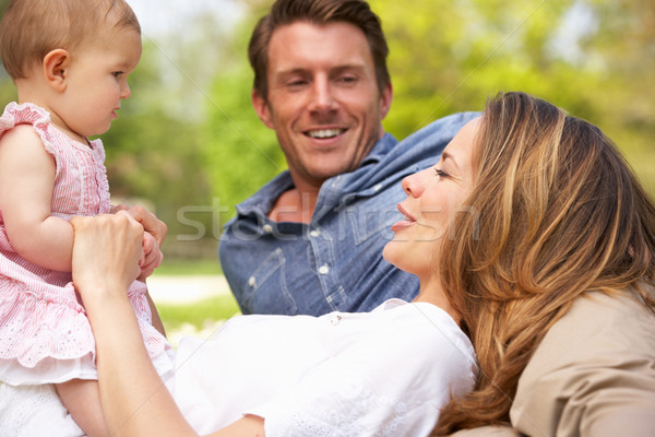 Parents With Baby Girl Sitting In Field Of Summer Flowers Stock photo © monkey_business