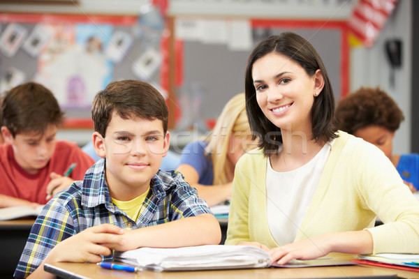 Stock photo: Teacher Helping Pupils Studying At Desks In Classroom