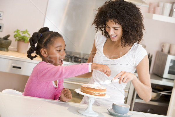 Woman and young girl in kitchen icing a cake smiling Stock photo © monkey_business