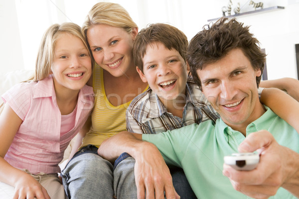 Family in living room with remote control smiling Stock photo © monkey_business