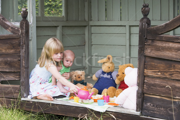 Stock photo: Young girl in shed with baby playing tea