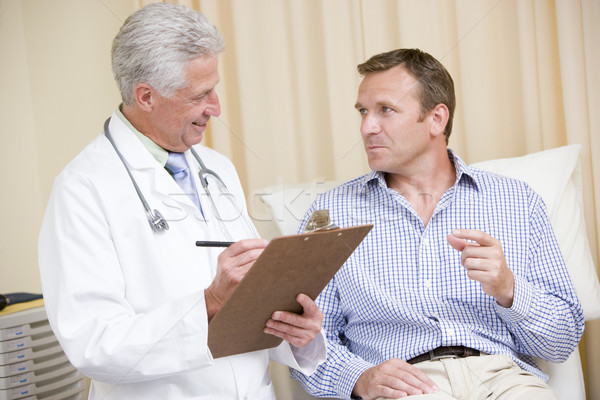 Doctor writing on clipboard while giving man checkup in exam roo Stock photo © monkey_business