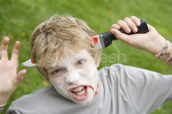 Young boy with scary Halloween make up and plastic knife through Stock photo © monkey_business