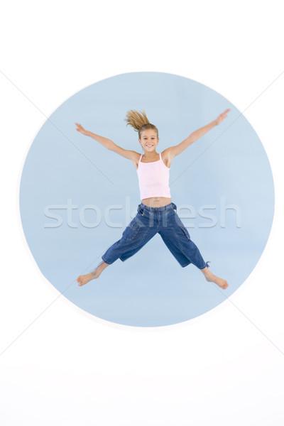 Zdjęcia stock: Młoda · dziewczyna · skoki · broni · na · zewnątrz · uśmiechnięty · dziewczyna