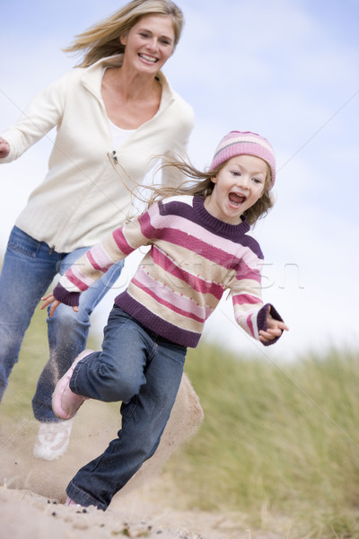 Mother and daughter running on beach smiling Stock photo © monkey_business