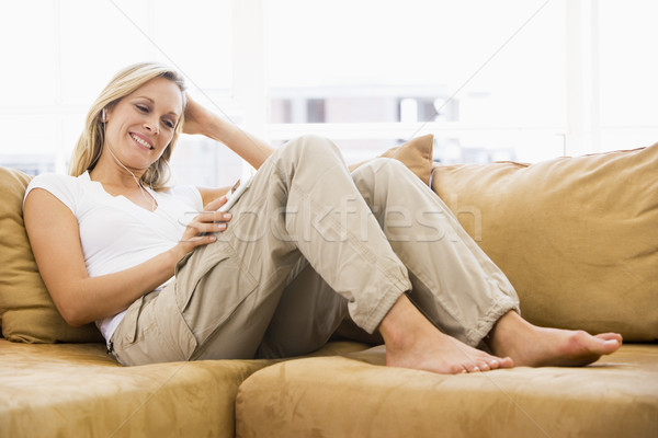 женщину гостиной прослушивании mp3-плеер улыбающаяся женщина улыбаясь Сток-фото © monkey_business