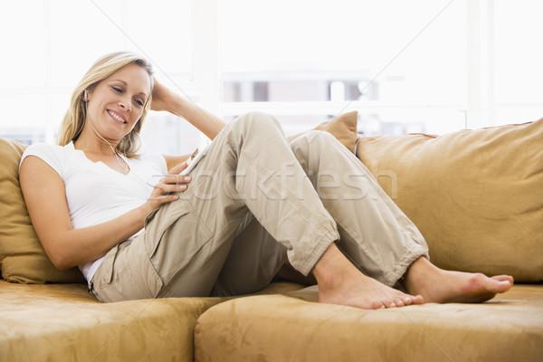 Vrouw woonkamer luisteren mp3-speler glimlachende vrouw glimlachend Stockfoto © monkey_business