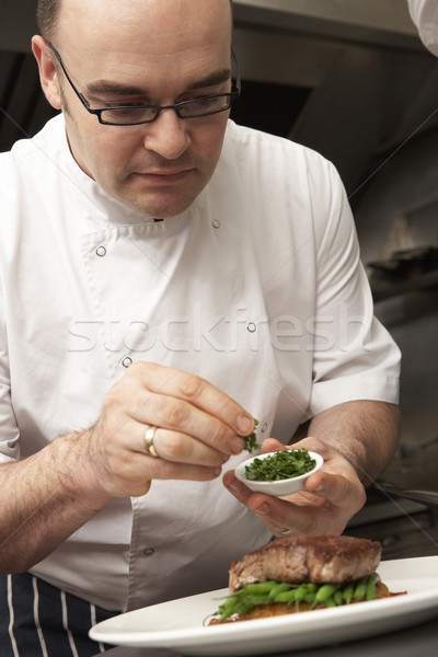 Stock photo: Chef Adding Seasoning To Dish In Restaurant Kitchen