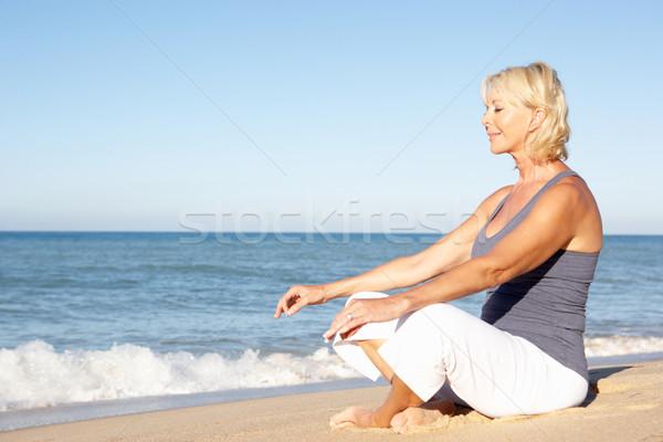 Senior Woman In Fitness Clothing Meditating On Beach Stock photo © monkey_business