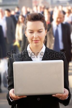 Male commuter in crowd using laptop Stock photo © monkey_business
