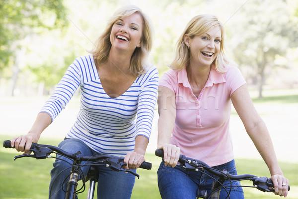 Foto stock: Dos · amigos · bicicletas · aire · libre · sonriendo · feliz