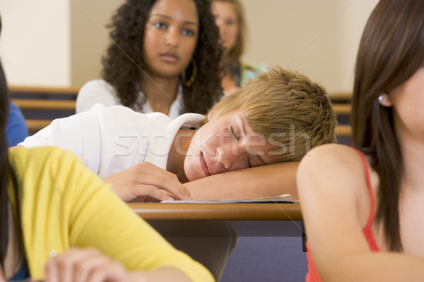 Male college student sleeping through a university lecture Stock photo © monkey_business