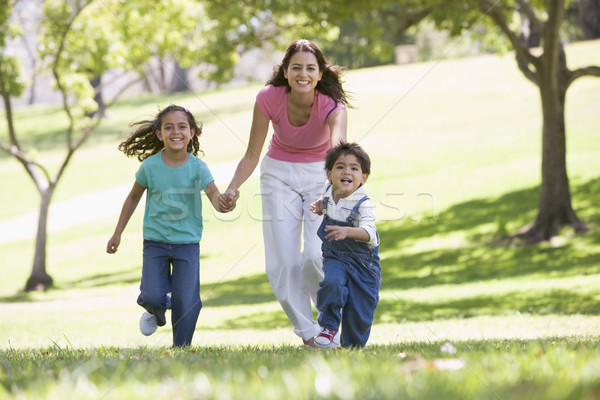 Woman with two young children running outdoors smiling Stock photo © monkey_business