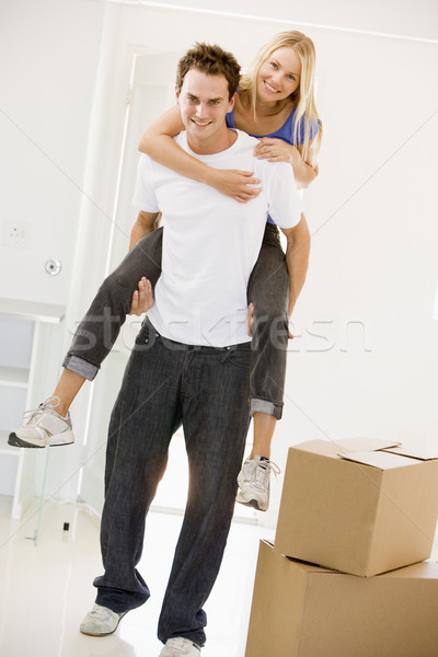Husband giving wife piggyback in new home smiling Stock photo © monkey_business
