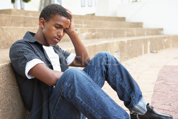 Unhappy Male Teenage Student Sitting Outside On College Steps Stock photo © monkey_business