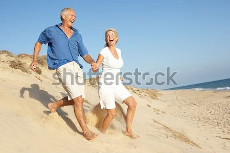 Stock photo: Senior Couple Enjoying Beach Holiday Running Down Dune