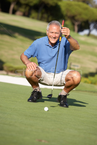 Senior Male Golfer On Golf Course Lining Up Putt On Green Stock photo © monkey_business