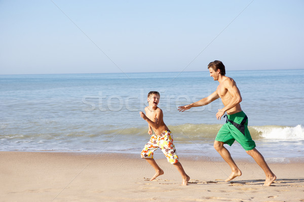 Father chasing young boy on beach Stock photo © monkey_business