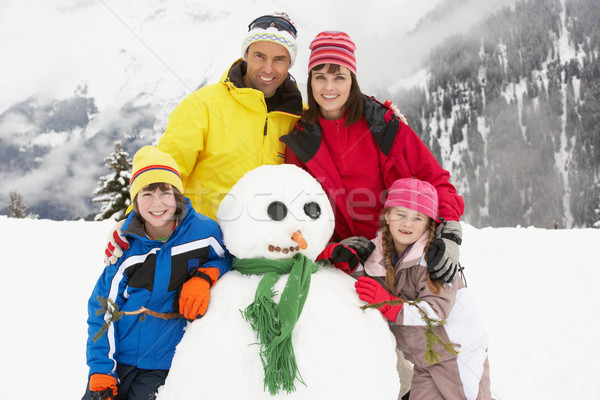 Stock photo: Family Building Snowman On Ski Holiday In Mountains