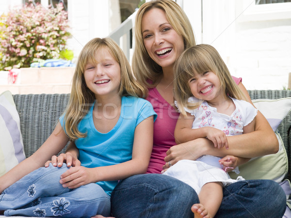 Woman and two young girls sitting on patio smiling Stock photo © monkey_business