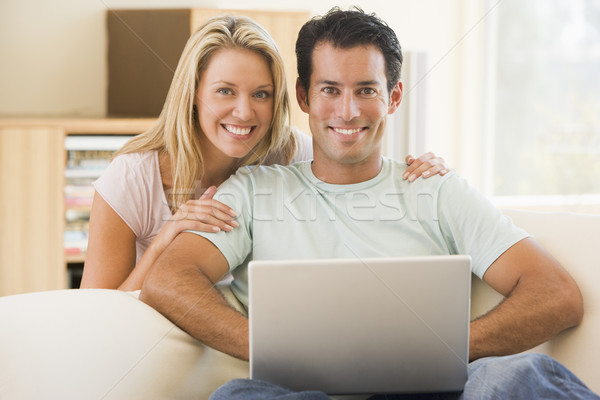 Couple in living room using laptop smiling Stock photo © monkey_business