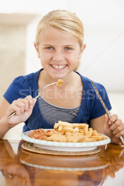 Jeune fille manger poissons puces souriant Photo stock © monkey_business
